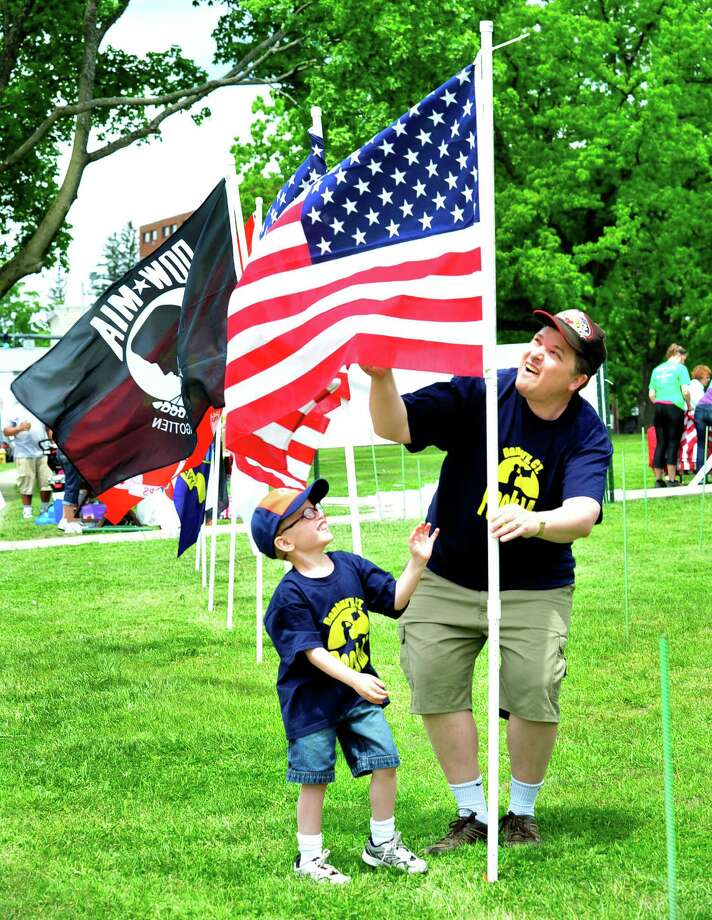 "Jay Mosteller helps his son, Jacob, 5, as the Kiwanis Club of Greater Danbury Foundation puts up a ""Field of Honor"" of 200 American Flags to honor veterans, at the War Memorial in Danbury, Conn. Saturday, May 18, 2013. Photo: Michael Duffy / The News-Times"