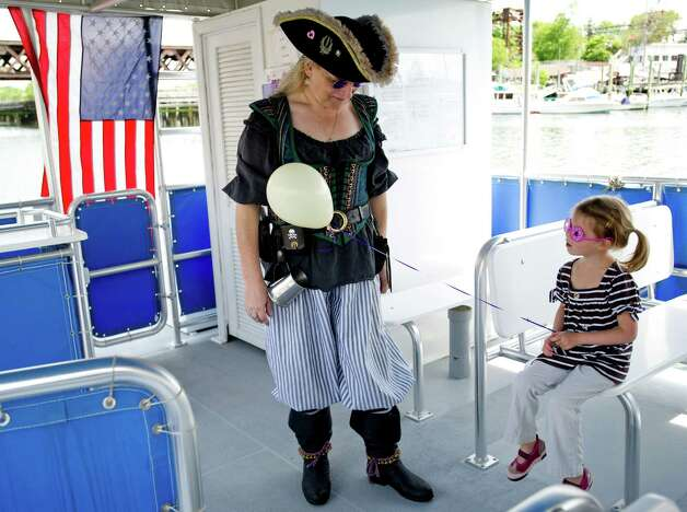 Pirate Rachelle Hayes talks to Annie Grimm, 4, during the Norwalk Seaport Association's Commissioning Day event to open the season in Norwalk, Conn., on Saturday, May 18, 2013. Photo: Lindsay Perry / Stamford Advocate