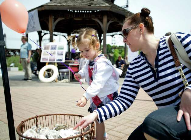 Kristi Mills and her daughter, Sawyer, 2, look at oyster shells during the Norwalk Seaport Association's Commissioning Day event to open the season in Norwalk, Conn., on Saturday, May 18, 2013. Photo: Lindsay Perry / Stamford Advocate