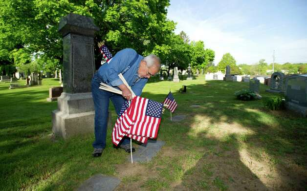 Charles Trudeau volunteer placing flags on the gravestones of veterans at St. John Cemetery in Darien on Saturday, May 18, 2013. Photo: Lindsay Perry / Stamford Advocate
