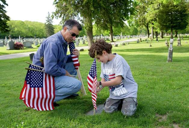 State Senator Carlo Leone and his son, Sam, 8, volunteer placing flags on the gravestones of veterans at St. John Cemetery in Darien on Saturday, May 18, 2013. Photo: Lindsay Perry / Stamford Advocate