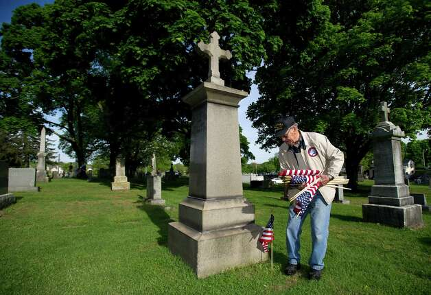 Fred DiSilvio volunteers placing flags on the gravestones of veterans at St. John Cemetery in Darien on Saturday, May 18, 2013. Photo: Lindsay Perry / Stamford Advocate