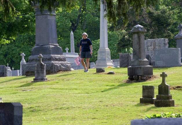 A volunteer places flags on the gravestones of veterans at St. John Cemetery in Darien on Saturday, May 18, 2013. Photo: Lindsay Perry / Stamford Advocate