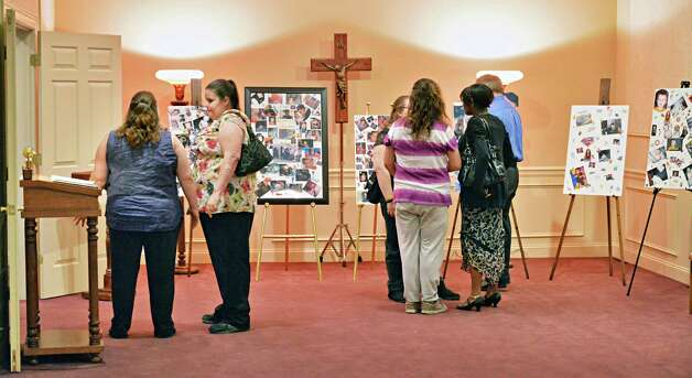 Mourners look over memorials to the Terry family, lost in a fatal house fire earlier this month, during funeral services at Bond Funeral Home in Schenectady, NY Saturday May 18, 2013.  (John Carl D'Annibale / Times Union) Photo: John Carl D'Annibale / 00022472A