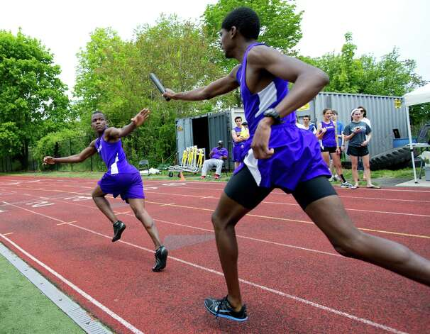 Westhill's Sherlson Petiphat receives the baton from Kajon Woodfine during Saturday's city track championship meet at Westhill High School on May 18, 2013. Photo: Lindsay Perry / Stamford Advocate
