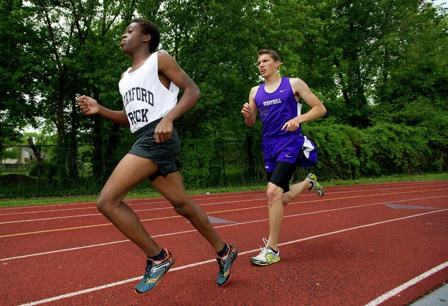 Pierre-Dens Fils, left, of Stamford, and Wyatt Grant, right, of Westhill, run during Saturday's city track championship meet at Westhill High School on May 18, 2013. Photo: Lindsay Perry / Stamford Advocate