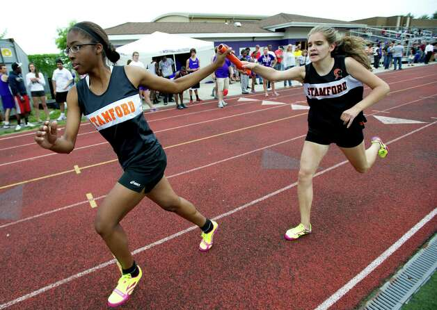 Stamford's Julia Kovalskiy hands off the baton to Sabina Pierre-Louis during Saturday's city track championship meet at Westhill High School on May 18, 2013. Photo: Lindsay Perry / Stamford Advocate