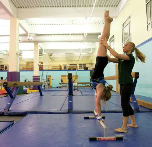 Kylie Cohen practices her uneven bar technique with Coach Arianna Mallardi at Chelsea Piers Connecticut on March 12, 2013. Photo: Lindsay Perry / Stamford Advocate
