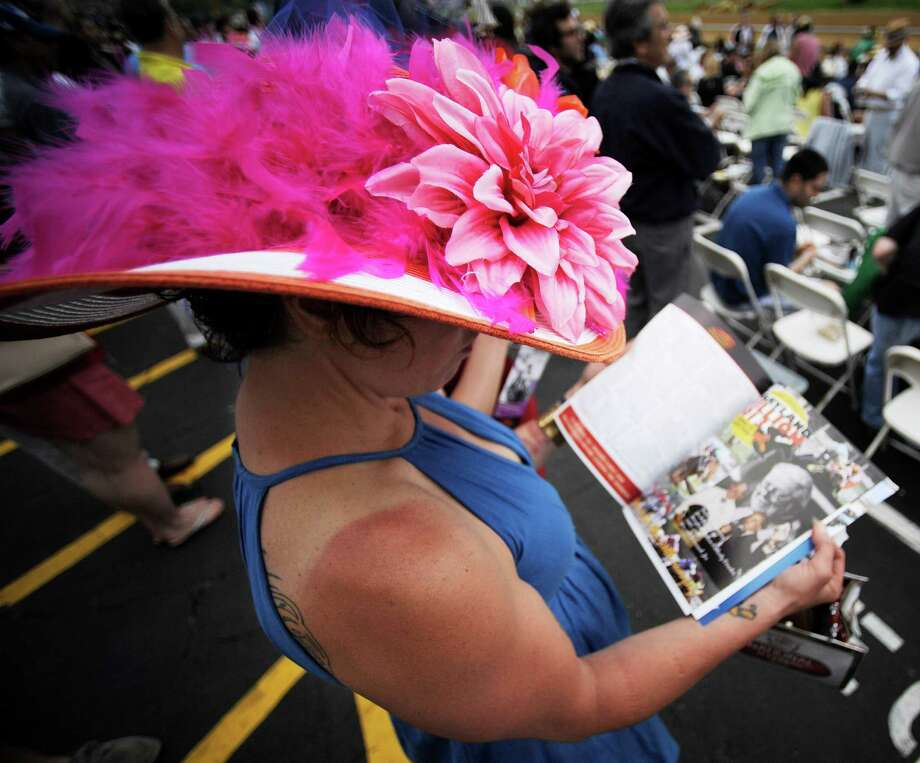 Lisa Scotti, of Baltimore, reads hhere program before the sixth race at Pimlico Race Course, Saturday, May 18, 2013, in Baltimore. The 138th Preakness Stakes horse race takes place Saturday. Photo: Mike Stewart