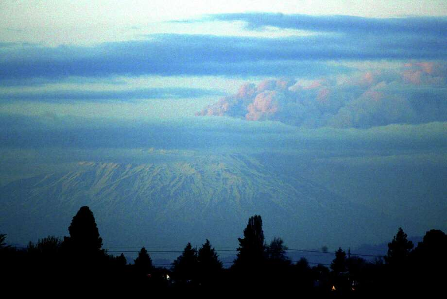 Mount St. Helens is seen in this view from the top of a hotel in Portland on March 8, 2005. The mountain released a towering column of steam and ash thousands of feet into the air as seismic activity signaled the reawakening of the 9,677-foot mountain. Photo: Craig Mitchelldyer, Getty Images / 2005 Getty Images