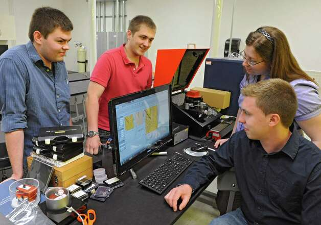 Clockwise from left, B.S. Nanoscale Engineering students Samuel LaGasse of Niskayuna, Leigh Lydecker IV of Newburgh, Nicole Palmer of South Glens Falls and Michael Briggs of Cohoes gather around a computer in a lab at Albany NanoTech Wednesday, May 15, 2013 in Albany, N.Y. They are the first undergrads to graduate from Albany NanoTech.  (Lori Van Buren / Times Union) Photo: Lori Van Buren / 00022447A