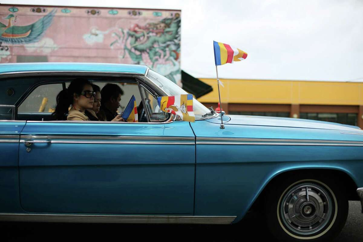 Participants ride in a classic car during a parade in the International District celebrating the birth of Buddha. Dozens of people honored Buddha by marching through the streets of the International District. Photographed on Saturday, May 18, 2013.