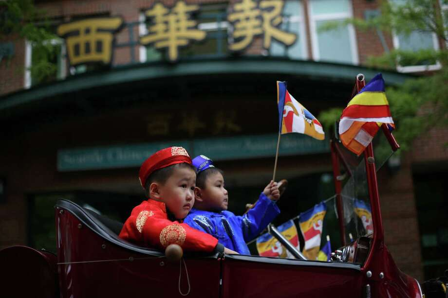 Thu Thang, 4, left, and Tom Thang, 3, wait to ride in a car during a parade in the International District celebrating the birth of Buddha. Dozens of people honored Buddha by marching through the streets of the International District. Photographed on Saturday, May 18, 2013. Photo: JOSHUA TRUJILLO, SEATTLEPI.COM / SEATTLEPI.COM