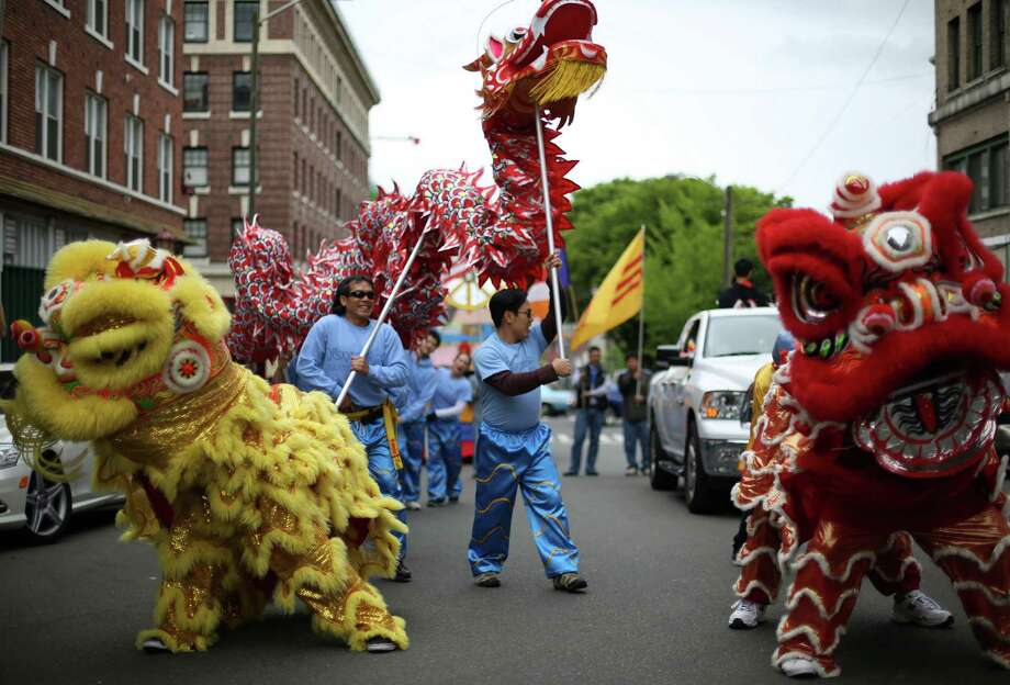 Lion and dragon dancers perform during a parade in the International District celebrating the birth of Buddha. Dozens of people honored Buddha by marching through the streets of the International District. Photographed on Saturday, May 18, 2013. Photo: JOSHUA TRUJILLO, SEATTLEPI.COM / SEATTLEPI.COM