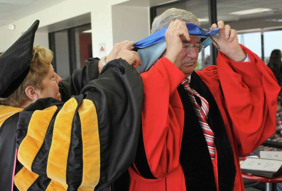 Back at the Red Room to get ready for the second ceremony,  President Jimmy Simmons, right, gets help from Brenda Nichols, left, Dean of Arts and Sciences, as he gets dressed again.  Simmons presided over his last two Commencement Ceremonies Saturday as President of Lamar University. He was also the Keynote speaker. When he finished Saturday afternoon, he was proud to say that over his years as President, including all the commencements,  he has shook 30, 245 graduate's hands as they walked across the stage.    Saturday's 1,605 graduates, was the largest graduating class in Lamar's history.  Dave Ryan/The Enterprise Photo: Dave Ryan