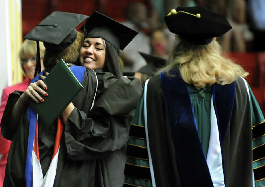 Graduate Kathryn Dahlgren, center, receives a hug when she collects her diploma during The Sage Colleges commencement on Saturday, May 18, 2013, at Rensselaer Polytechnic Institute in Troy, N.Y. (Cindy Schultz / Times Union) Photo: Cindy Schultz / 10022130A