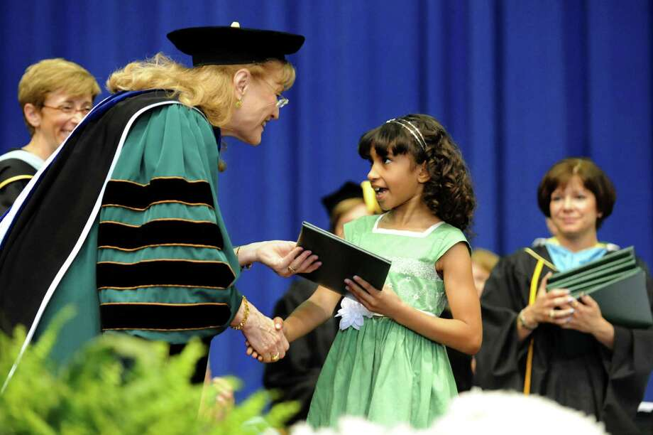 President Susan Scrimshaw, left, gives Stylianna Mantzouris, 7, a diploma on behalf of her mother, Sophia Mantzouris, during The Sage Colleges commencement on Saturday, May 18, 2013, at Rensselaer Polytechnic Institute in Troy, N.Y. Sophia is in the Air Force serving in Afghanistan. (Cindy Schultz / Times Union) Photo: Cindy Schultz / 10022130A