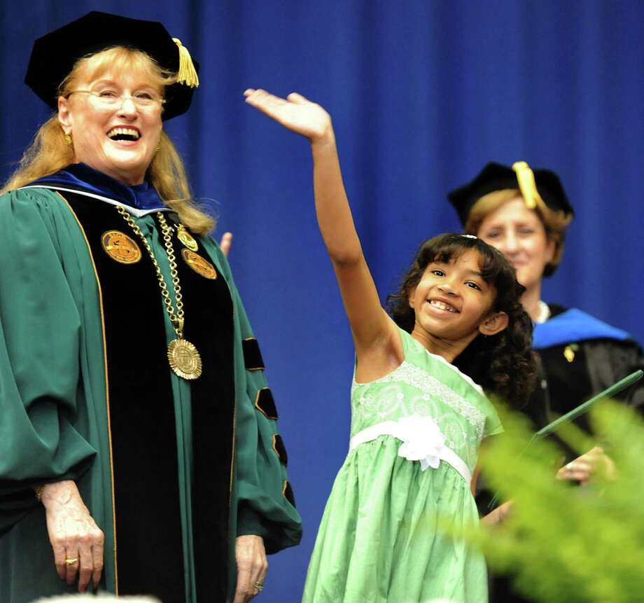 Stylianna Mantzouris, 7, center, gives a wave after collecting a diploma on behalf of her mother, Sophia Mantzouris, during The Sage Colleges commencement on Saturday, May 18, 2013, at Rensselaer Polytechnic Institute in Troy, N.Y. Sophia is in the Air Force serving in Afghanistan. At left is college president Susan Scrimshaw. (Cindy Schultz / Times Union) Photo: Cindy Schultz / 10022130A