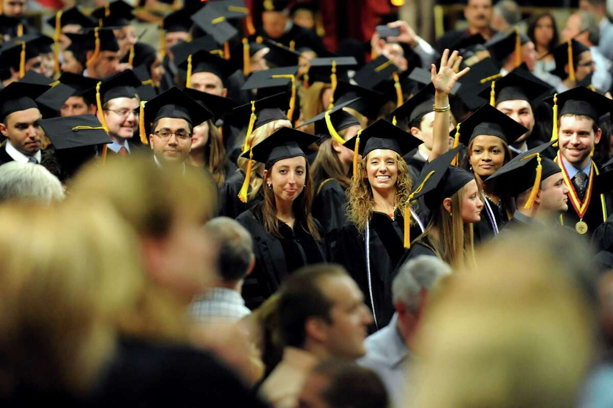 A graduate waves to loved ones at the start of the Albany College of Pharmacy college commencement on Saturday, May 18, 2013, at the Convention Center in Albany, N.Y. (Cindy Schultz / Times Union)