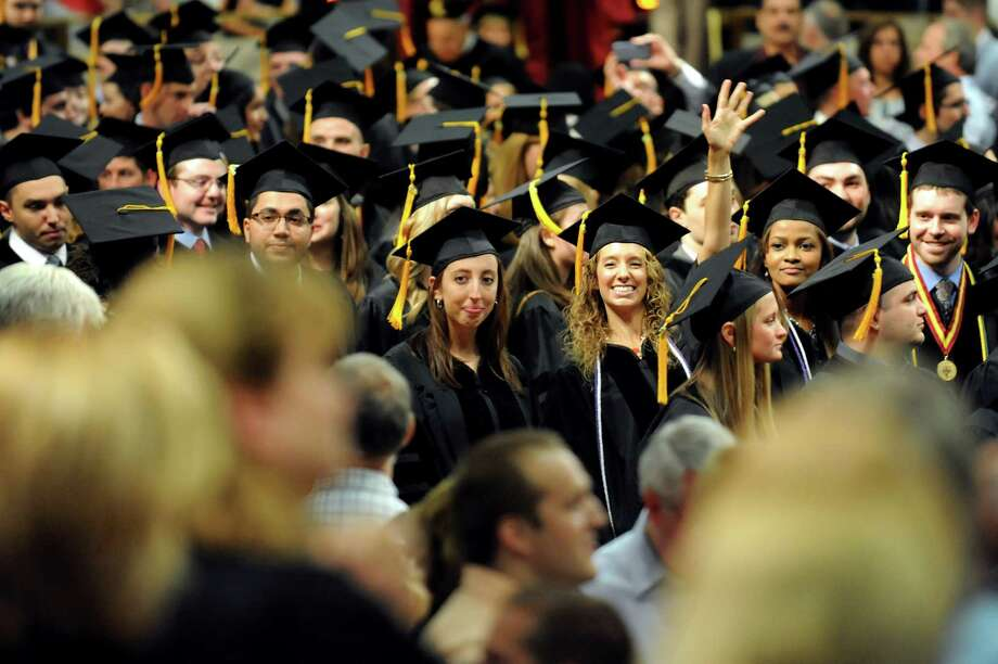 A graduate waves to loved ones at the start of the Albany College of Pharmacy college commencement on Saturday, May 18, 2013, at the Convention Center in Albany, N.Y. (Cindy Schultz / Times Union) Photo: Cindy Schultz / 10022116A