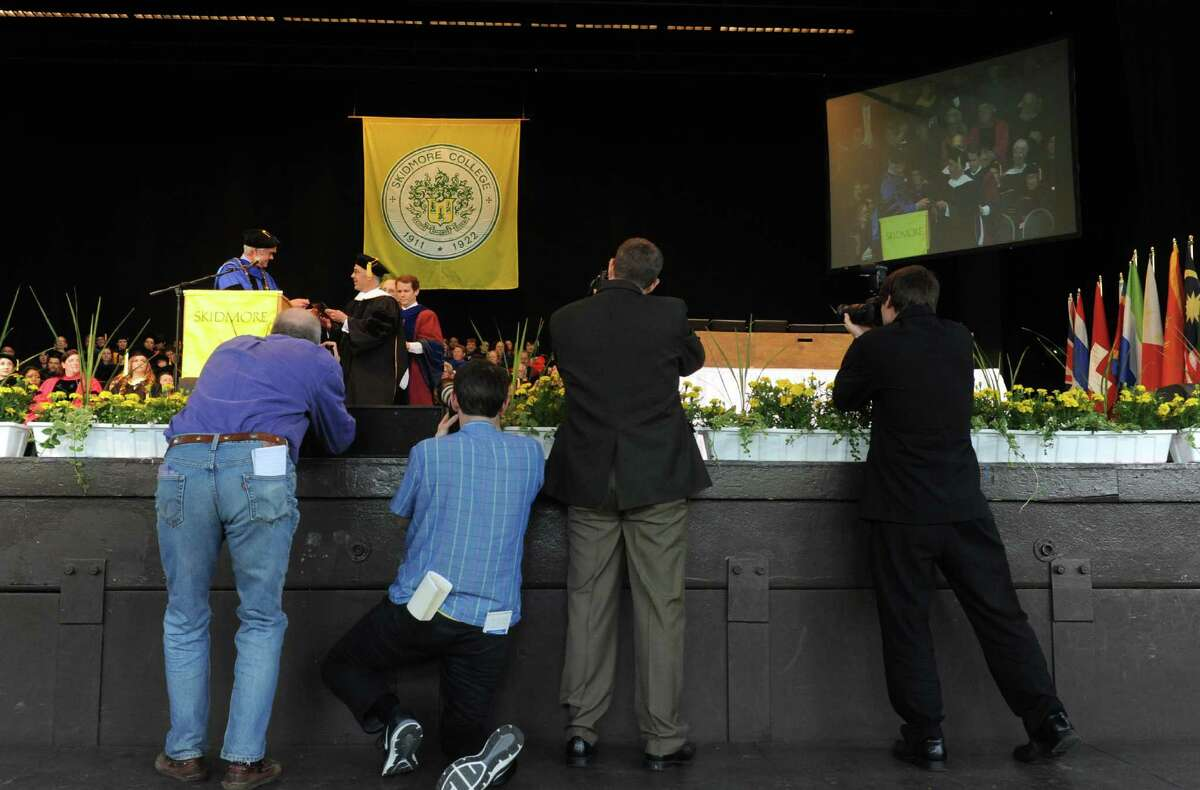 Photographers take their shots as Skidmore president Philip A. Glotzbach presents David Brooks with an honorary Doctors of Letters degree during the Skidmore 102nd college commencement at SPAC on Saturday May 18, 2013 in Saratoga Springs, N.Y. (Michael P. Farrell/Times Union)