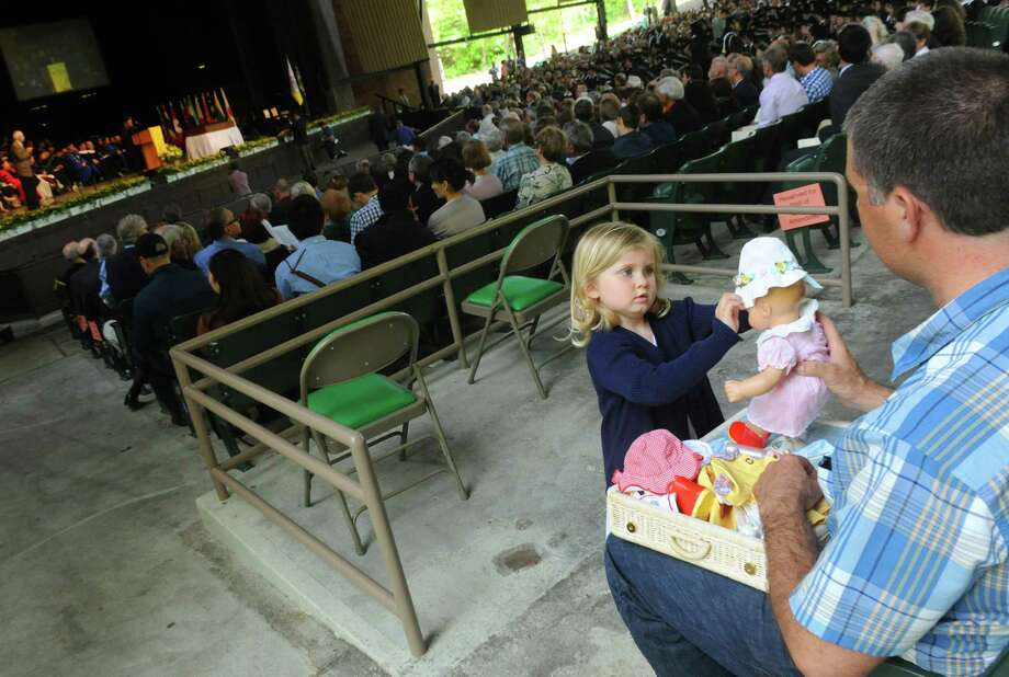 Three-year-old Cadence Guerdat dresses her doll while she waits for her aunt Alex Goossen to graduate during the Skidmore 102nd college commencement at SPAC on Saturday May 18, 2013 in Saratoga Springs, N.Y. (Michael P. Farrell/Times Union) Photo: Michael P. Farrell