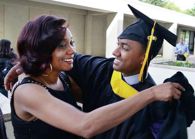Masters degree grad Yasmani Isaac, at right, gets a hug from his mother Yohanka Hernandez before the start of UAlbany Graduate college commencement ceremonies in Albany, NY Saturday May 18, 2013.  (John Carl D'Annibale / Times Union) Photo: John Carl D'Annibale / 10022137A