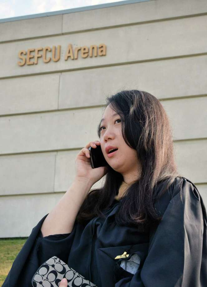 Masters degree graduate Ye Liu of Albany uses a cell phone to call for different shoes before the start of UAlbany Graduate college commencement ceremonies in Albany, NY Saturday May 18, 2013.  (John Carl D'Annibale / Times Union) Photo: John Carl D'Annibale / 10022137A