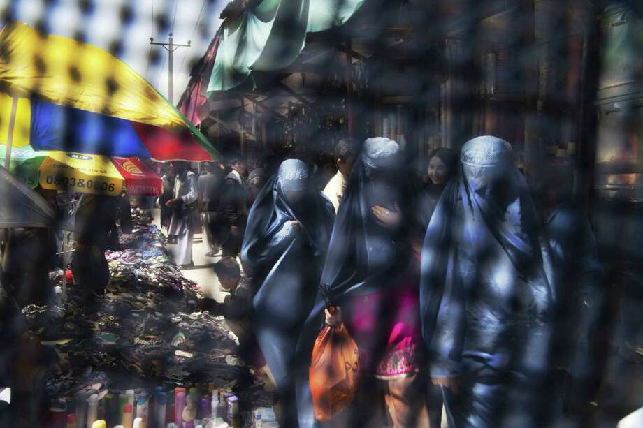 A photo taken through a burqa shows Afghan women in a Kabul market. A push to address the nation's law for protections for women has split Afghanistan's small women's rights community. Photo: Associated Press File Photo