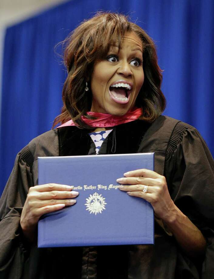 First lady Michelle Obama jokes with a student as she hands out diplomas during the graduation ceremony for Martin Luther King, Jr. Academic Magnet High School on Saturday, May 18, 2013, in Nashville, Tenn. (AP Photo/Mark Humphrey) Photo: Mark Humphrey