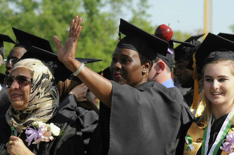 Ruth Ann Turner-Greenwwod, center, of Albany with an apple on her cap waves to family during the HVCC 56th annual college commencement  on Saturday May 18, 2013 in Troy, N.Y. (Michael P. Farrell/Times Union) Photo: Michael P. Farrell