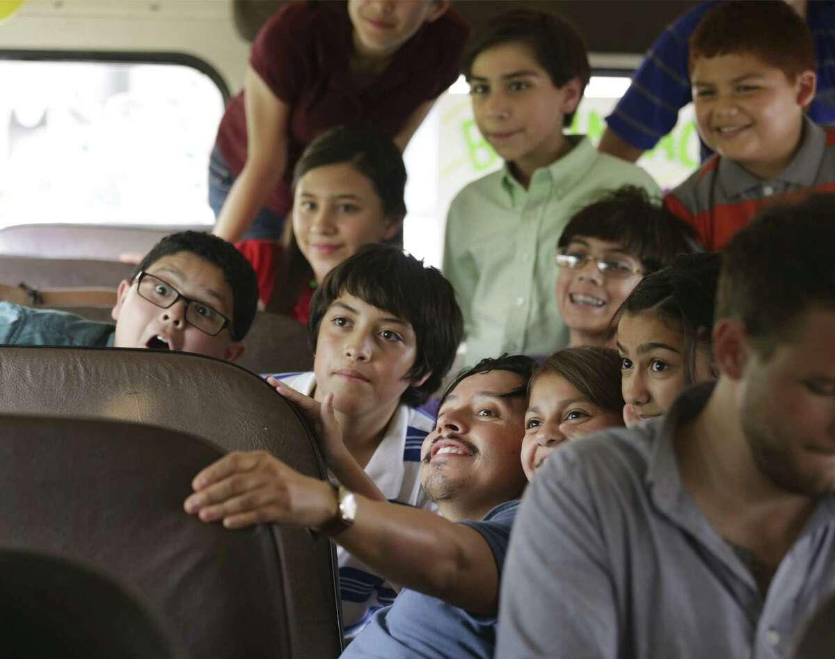 Efren Ramirez (lower center) clowns with young actors on a school bus between shots. The character Ramirez plays was the elder Guajardo.