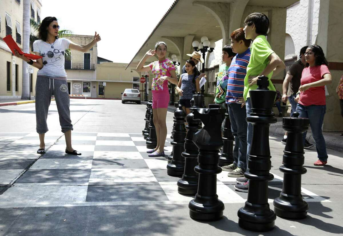 """""""Endgame"""" director Carmen Marron (left) gives pointers to actors during filming of the movie about the chess team from Brownsville in the city's Market Square. The screenplay that's based on the team's rise to prominence in the chess world was penned by Hector Salinas, an attorney with a penchant for writing."""