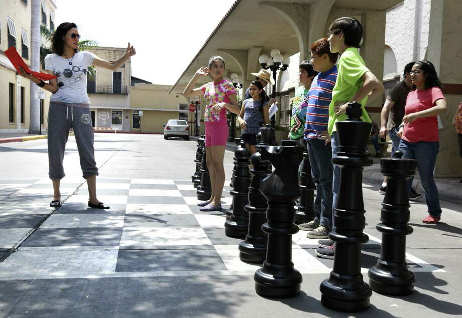 """""""Endgame"""" director Carmen Marron (left) gives pointers to actors during filming of the movie about the chess team from Brownsville in the city's Market Square. The screenplay that's based on the team's rise to prominence in the chess world was penned by Hector Salinas, an attorney with a penchant for writing. Photo: Bob Owen / San Antonio Express-News"""