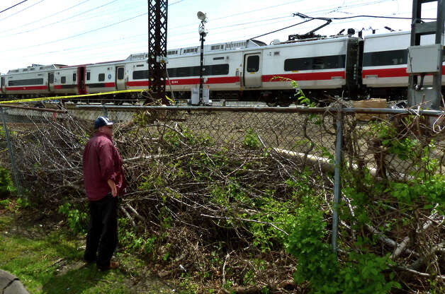 An onlooker checks out the Metro-North commuter trains involved in Friday's train derailment in Bridgeport, Conn. on Saturday May 18, 2013. Photo: Christian Abraham / Connecticut Post