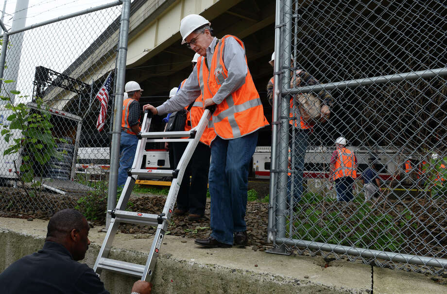 Metro-North Railroad President Howard Permut gets ready to descend a ladder after touring the scene of Friday's train derailment in Bridgeport, Conn. on Saturday May 18, 2013. Photo: Christian Abraham / Connecticut Post
