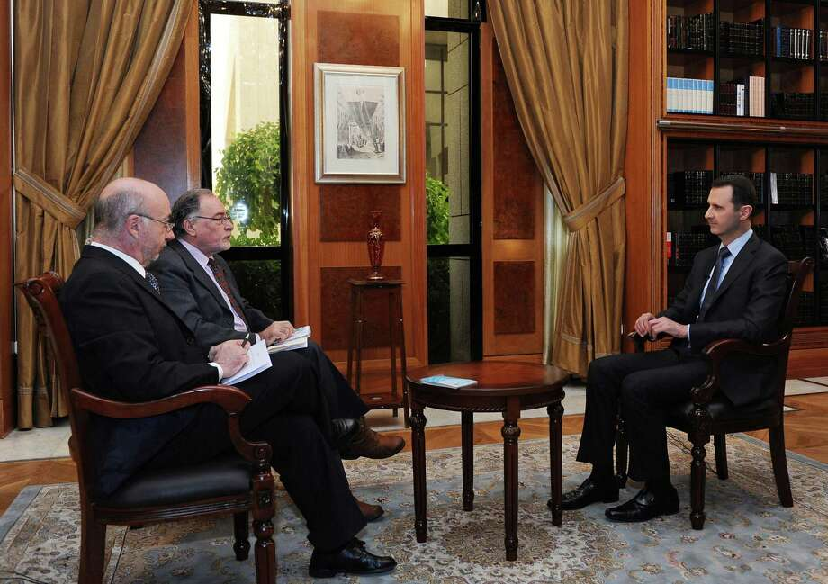 Syrian President Bashar al-Assad (right) speaks during an interview in Damascus with the Argentine newspaper Clarin and the Argentine state news agency, Telam. Photo: SANA / Associated Press