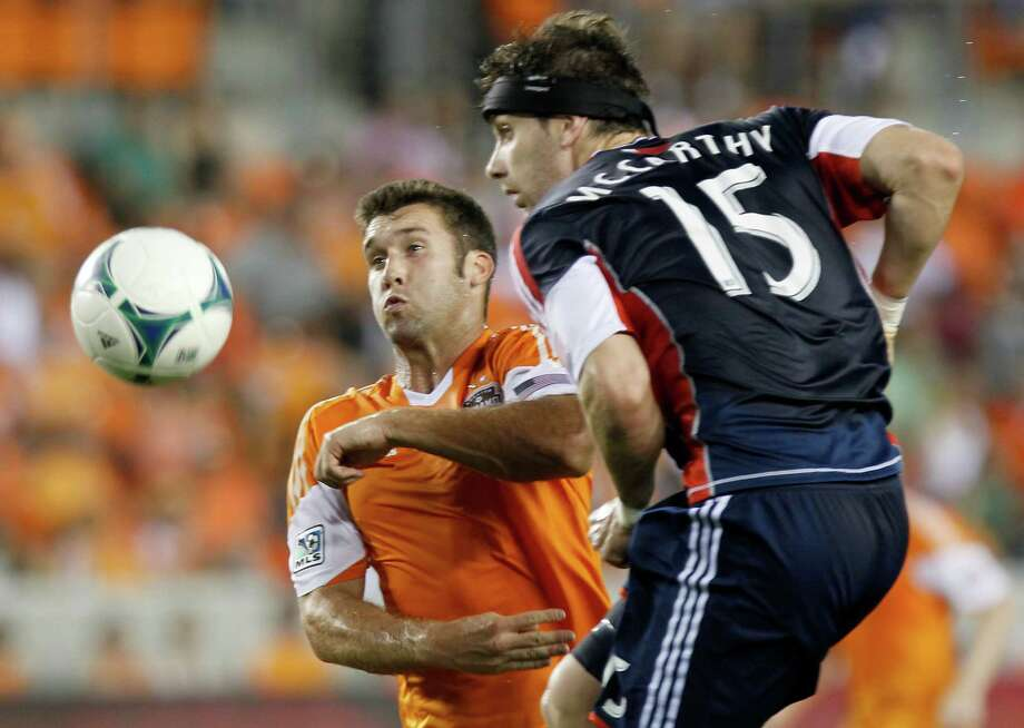 5/18/13: Houston Dynamo forward Will Bruin (12) heads the ball away from New England Revolution defender/midfielder Stephen McCarthy (15) in the first half at BBVA Compass Stadium in Houston, Texas. Photo: Thomas B. Shea, For The Chronicle / © 2013 Thomas B. Shea