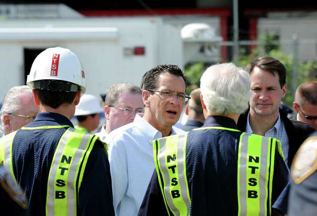 Gov. Dannel Malloy and Congressman Jim Himes talk with NTSB representatives at a staging area near the scene of Friday evening's Metro-North train collision in Bridgeport, Conn. Investigators from National Transportation Safety Board were on the scene on Saturday May 18, 2013 to find the cause of the accident that left more than 60 people injured. Photo: Cathy Zuraw / Connecticut Post