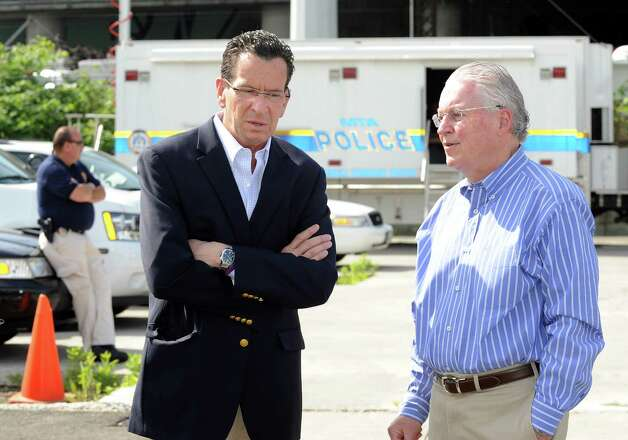 Gov. Dannel Malloy talks with Fairfield First Selectman Michael Tetreau at a staging area near the scene of Friday evening's Metro-North train collision in Bridgeport, Conn. Investigators from National Transportation Safety Board were on the scene on Saturday May 18, 2013 to find the cause of the accident that left more than 60 people injured. Photo: Cathy Zuraw / Connecticut Post