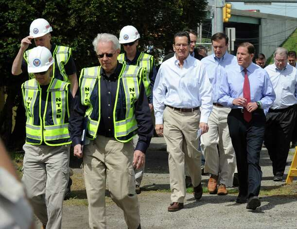Investigators from National Transportation Safety Board, Gov. Dannel Malloy, Senators Chris Murphy and Dick Blumenthal walk to a press conference after touring the scene of Friday evening's Metro-North train collision in Bridgeport, Conn. Investigators were on the scene Saturday May 18, 2013 to find the cause of the accident that left more than 60 people injured. Photo: Cathy Zuraw / Connecticut Post