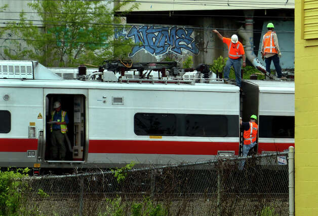 Metro-North Railroad employees work at the scene of Friday's train derailment in Bridgeport, Conn. on Saturday May 18, 2013. Photo: Christian Abraham / Connecticut Post