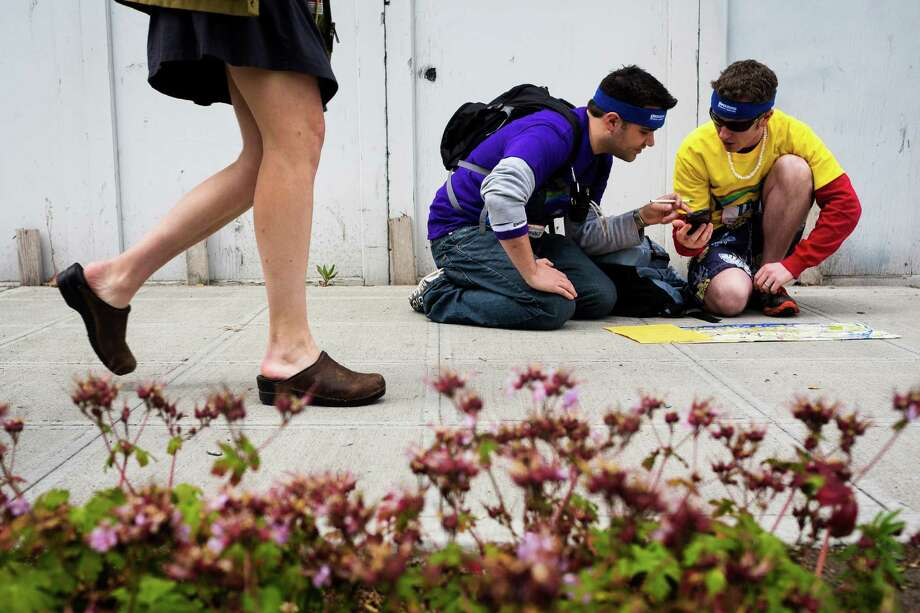 Runners utilize a hint sheet and smartphones to decipher their next move during the Great Urban Race Saturday, May 18, 2013, in Seattle. An estimated 400 runners competed. Teams of runners were given five hours to visit 12 unique checkpoints and return to the starting point. The top three winning teams went on to compete in the national tour. Photo: JORDAN STEAD, SEATTLEPI.COM / SEATTLEPI.COM