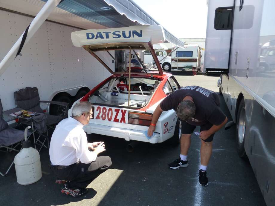 Les Cannaday (right), crew chief for the 1979 Datsun 280-ZX of actor and comedian Adam Carolla, talks to brake fluid expert Michael Wachholz.