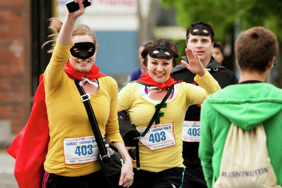 Contestants sprint between stations during the Great Urban Race Saturday, May 18, 2013, in Seattle. An estimated 400 runners competed. Teams of runners were given five hours to visit 12 unique checkpoints and return to the starting point. The top three winning teams went on to compete in the national tour. Photo: JORDAN STEAD, SEATTLEPI.COM / SEATTLEPI.COM