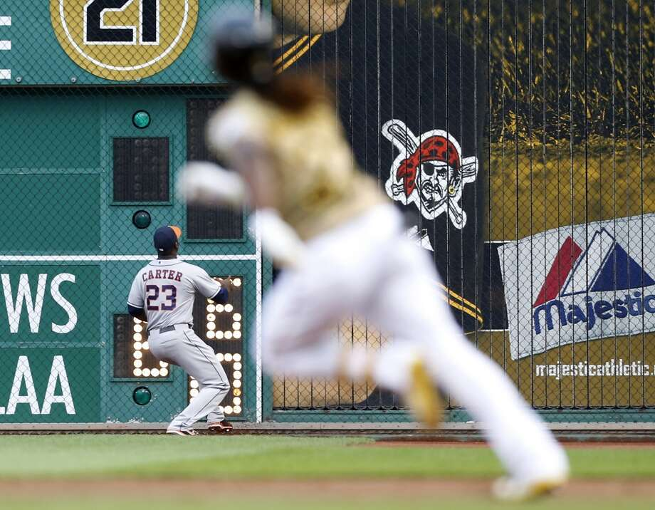 Chris Carter (23) looks for the ball as Andrew McCutchen heads for second.