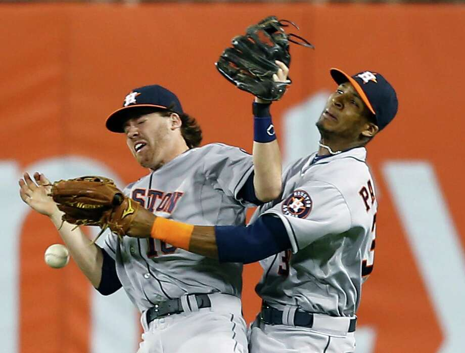 It has been a comedy of errors in the field for the Astros, such as when shortstop Jake Elmore, left, and outfielder Jimmy Paredes collided and the ball dropped. Photo: Keith Srakocic, STF / AP