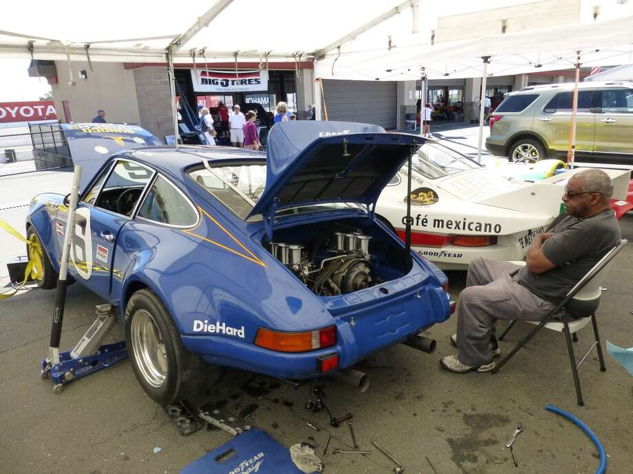 Tony Miller, a seasoned Porsche mechanic, has spent 41 years rebuilding Porsche engines. Here, he sits between two 1973 Porsche RSR racers owned by Jacob Shalet.