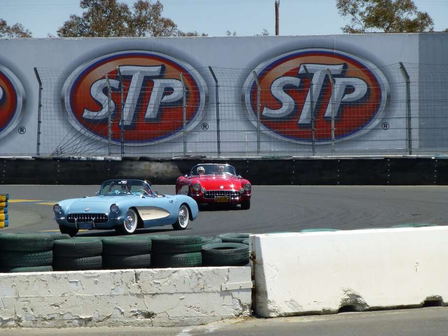 Two early Corvettes rounding the last corner before heading up the straightaway past the grandstand.