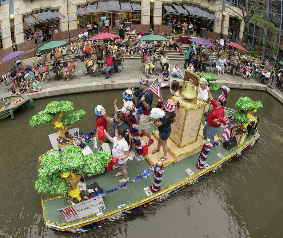 Participants on a float wave to spectators in Rivercenter lagoon during America's Armed Forces River Parade. Photo: Photos By Darren Abate / For The San Antonio Express-News